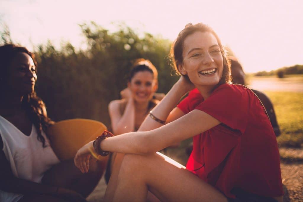Gruppe junger Freunde sitzt zusammen an einem sonnigen Tag
