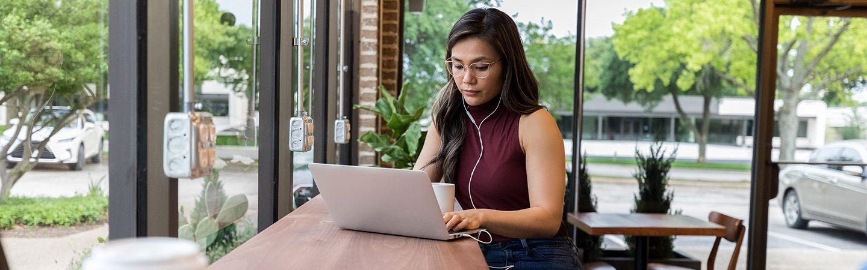 Richtig bewerben: Junge Frau verfasst Bewerbung am Laptop